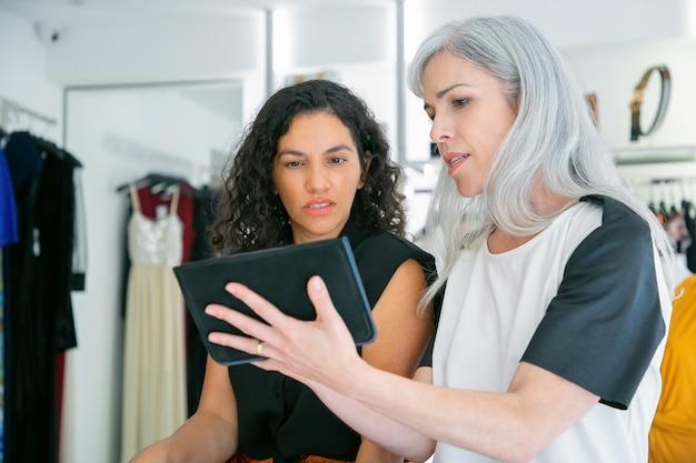 Klant en winkelbediende ontmoeten elkaar in de modewinkel, zitten samen en gebruiken tablet, bespreken kleding en aankopen. consumentisme of winkelconcept