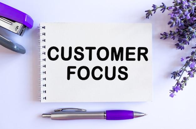Klant focus. bovenaanzicht van open lege kladblok met lavendel boeket op witte achtergrond