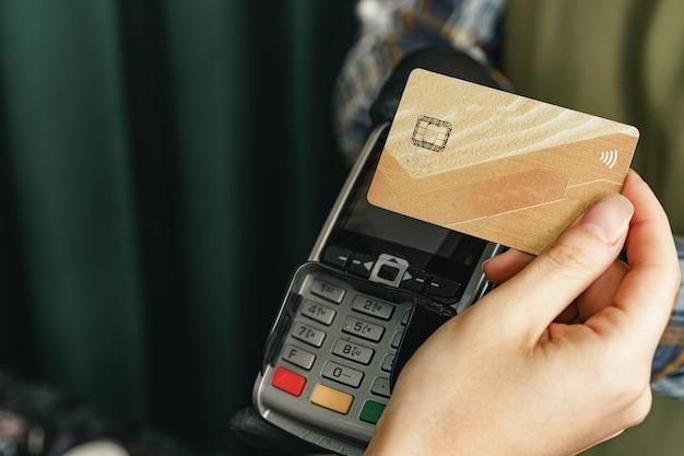 Klant gebruikt creditcard voor betaling in café of winkel per terminal met nfc-technologie zonder contant geld