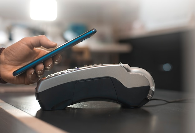 Klant hand betaalt met smartphone in de winkel met behulp van nfc-technologie. mobiele telefoon die de rekening betaalt met contactloze technologie.