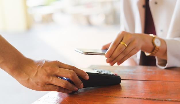 Klant hand met smartphone voor het betalen van rekening met behulp van betaalautomaat aan tafel