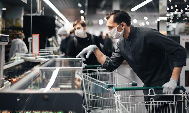 Klant in beschermende handschoenen die producten in een supermarkt kiest. hygiëne en gezondheidszorg