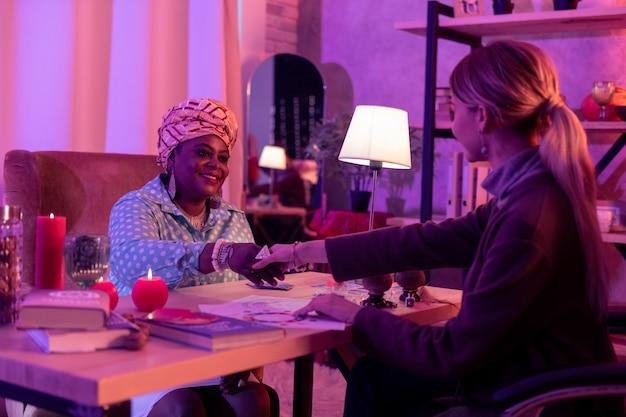 Klant in de salon. afro-amerikaanse mollige waarzegster met etnische hoofddeksels handen schudden met de klant