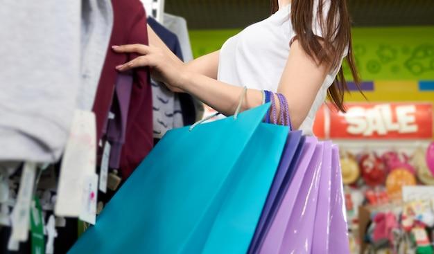 Klant met boodschappentassen in winkelcentrum kiezen van kleding.