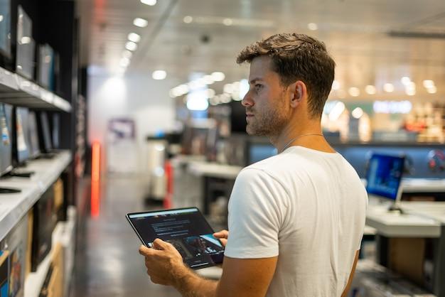 Klant met tablet die hardware in winkel kiest