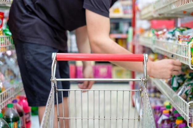 Klant met winkelwagentje product kiezen in de supermarkt