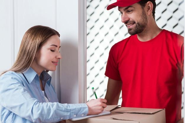 Klant ondertekent de levering en koerier die de doos vasthoudt