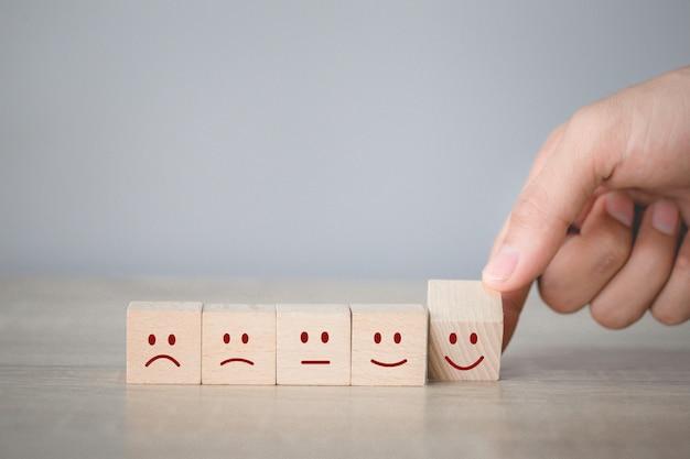 Klant te drukken smileygezicht emoticon op houten kubus, service rating, tevredenheid concept.