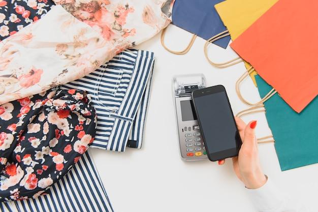 Klant via telefoon voor betaling aan eigenaar bij winkel, restaurant, cashless technologie en creditcardbetalingsconcept