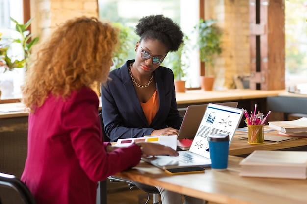Klanten contacteren. twee professionele interieurontwerpers die hun laptop gebruiken terwijl ze contact opnemen met klanten