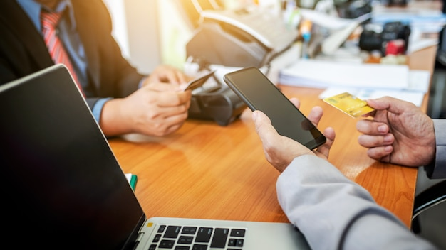 Klanten die rekenings financieel snel contant geld betalen door nfc-betalingspos technologie met mobiele app in smartphone.