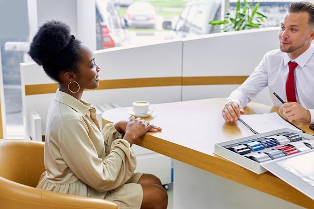 Klanten drinken een kopje koffie en voeren een vriendelijk gesprek met autodealer