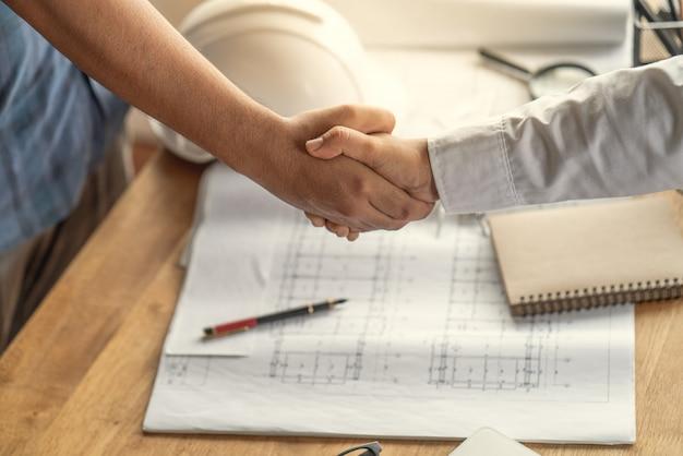 Klanten handdruk overeenkomst met de aannemer voor de bouw van huizen