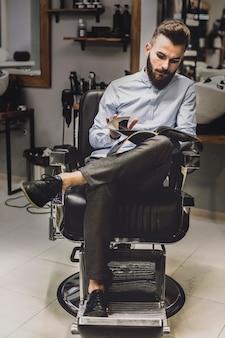 Klanten kijken magazine in barbershop