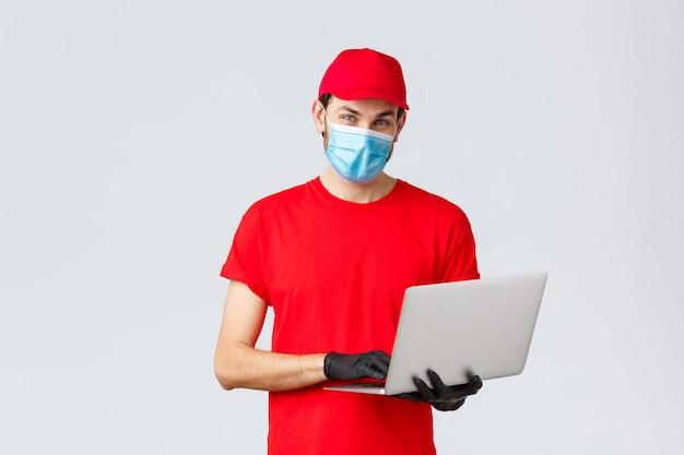 Klantenondersteuning, covid-19-bezorgpakketten, online bestellingenverwerkingsconcept. aangename bezorger in rood uniform, gezichtsmasker en handschoenen, met behulp van laptop en kijkcamera, bestelling verwerken