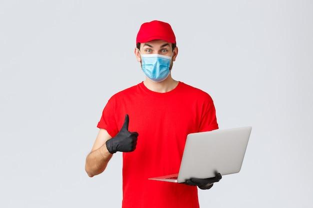 Klantenondersteuning, covid-19-bezorgpakketten, online bestellingenverwerkingsconcept. enthousiaste koerier in rode uniform thumbs-up leespromo op webpagina. bezorger houdt laptop vast, draagt masker en handschoenen