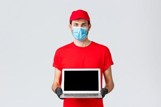 Klantenondersteuning, covid-19-bezorgpakketten, online bestellingenverwerkingsconcept. glimlachende koerier in rood uniform, gezichtsmasker en handschoenen, met de webpagina van het bedrijf op het laptopscherm