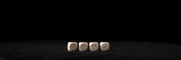 Klantenservicebeoordeling en feedback conceptueel beeld - vier houten blokken met een lachend, verdrietig en neutraal gezicht erop.