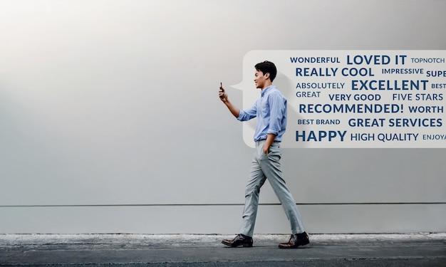 Klantervaring concept. positieve online recensie lezen via smartphone. glimlachende jonge zakenman met behulp van mobiele telefoon tijdens het wandelen door de muur van het stedelijk gebouw.