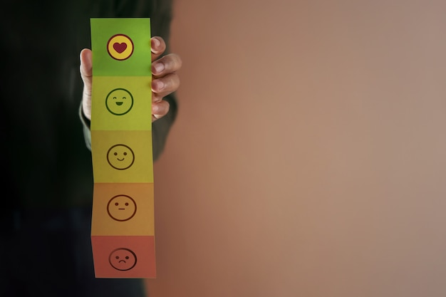 Klantervaring concept. tevreden klant geeft positieve recensie op gevouwen papier. feedbackpictogram van slecht naar uitstekend