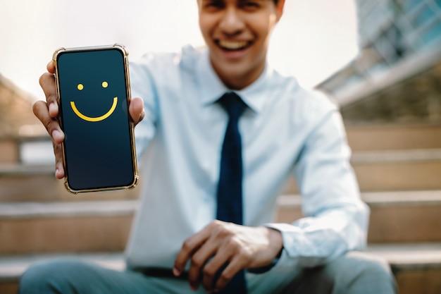 Klantervaringen concept. jonge zakenman die een blij gezicht icoon en positieve beoordeling via smartphone. klanttevredenheidsonderzoeken op mobiele telefoon. vooraanzicht