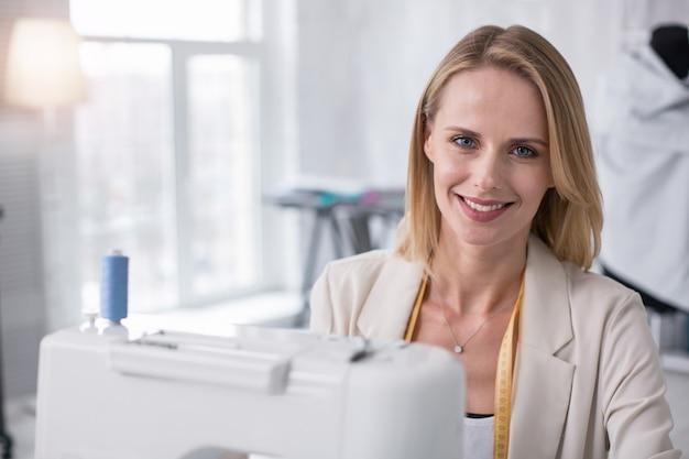 Klantgerichte focus. positieve vrouwelijke kleermaker grijnzend naar de camera tijdens het gebruik van de naaimachine