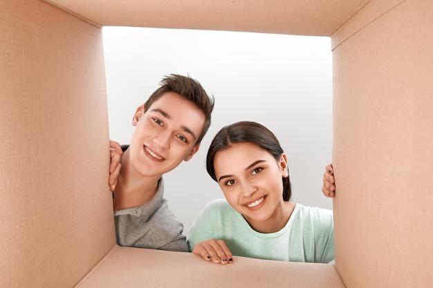 Klanttevredenheid is waardeloos lachende jongen en meisje die een kartonnen doos openen en naar binnen kijken