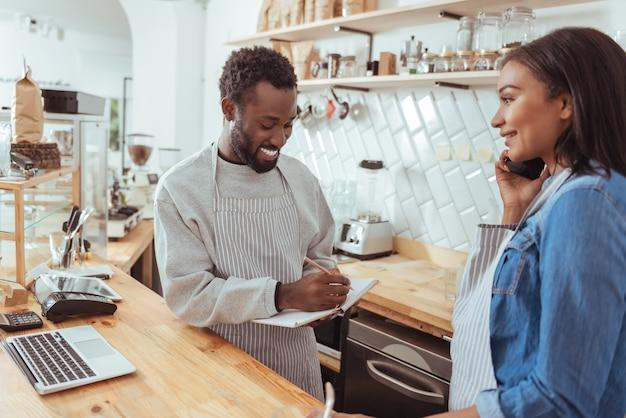 Klantvriendelijk. aangename jonge barista die achter de balie van het café staat en neerzet en de bestelling telefonisch wordt ontvangen en gedicteerd door zijn vrouwelijke collega