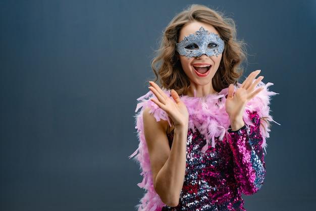Klap in je handen enthousiaste jonge vrouw in een glanzende paarse jurk met een boa in de nek