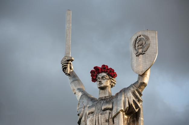 Klaprozen van geheugen. het monument mother motherland versierd met een krans van klaprozen op de dag van herdenking en verzoening in kiev, oekraïne