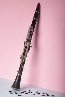 Klarinet met houten muzieknoten op blauwe en roze ruimte
