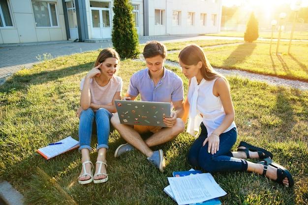 Klasgenoot, onderwijs en tienerconcept. vriendelijke studenten tieners met laptop