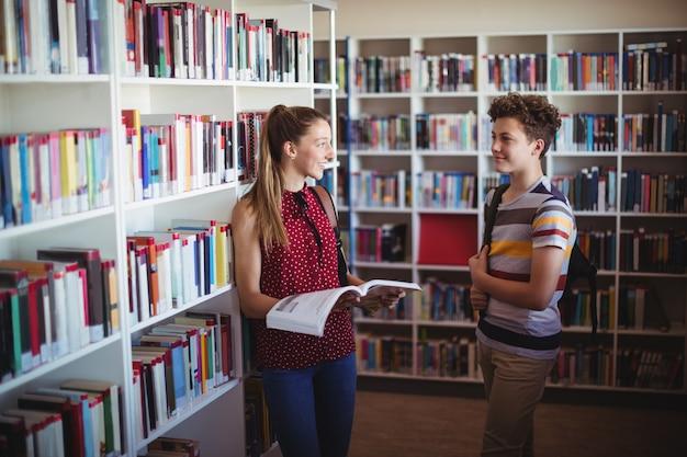 Klasgenoten communiceren met elkaar in de bibliotheek