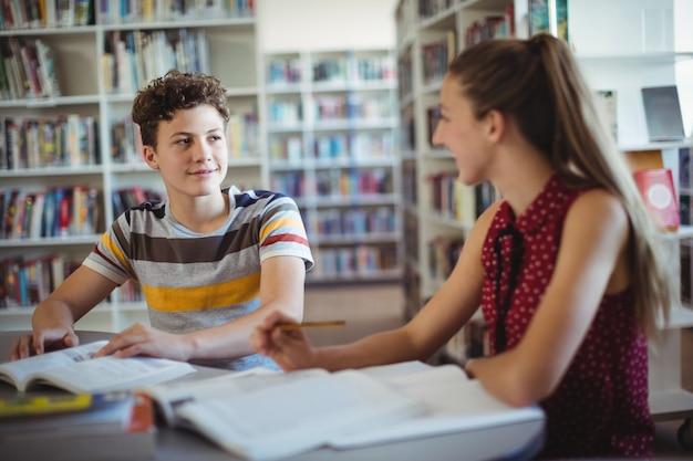Klasgenoten communiceren terwijl ze huiswerk maken in de bibliotheek