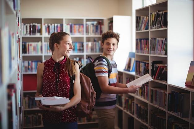 Klasgenoten communiceren tijdens het selecteren van een boek in de bibliotheek