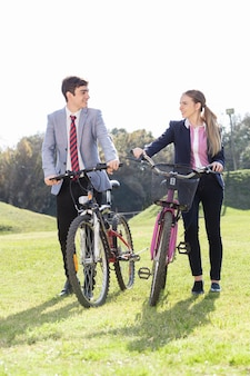 Klasgenoten praten en glimlachend naast hun fietsen