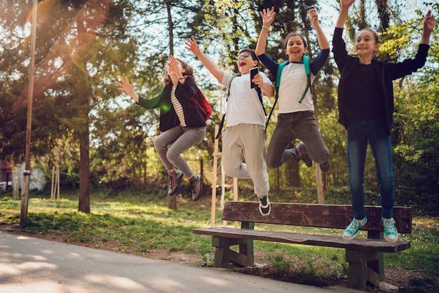 Klasgenoten springen van bankje op schoolplein