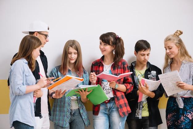 Klasgenoten staan met leerboeken