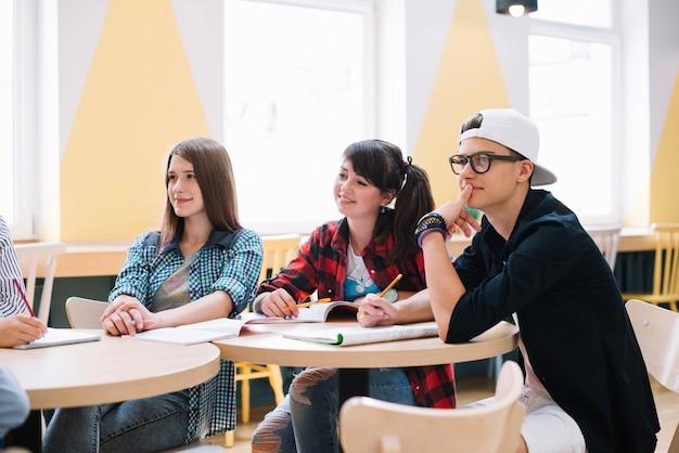 Klasgenoten zitten en leren aan de balie