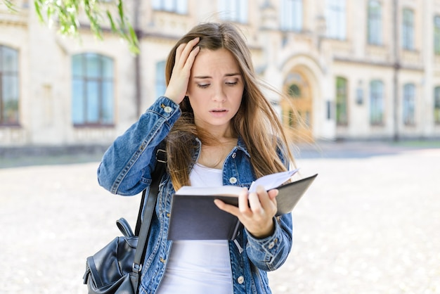 Klaslokaal moeilijk bang lui project niet klaar faalt huiswerkconcept close-up foto portret van verdrietig boos huilen doodsbang bang bang depressief meisje kijken naar boek in de hand hoofd aanraken