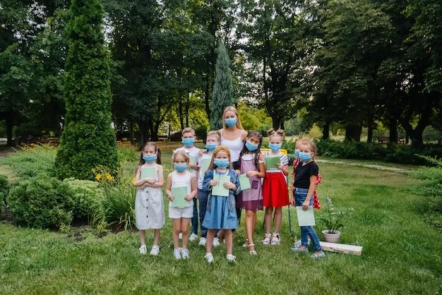 Klasse gemaskerde schoolkinderen die tijdens de epidemie buitentrainingen volgden