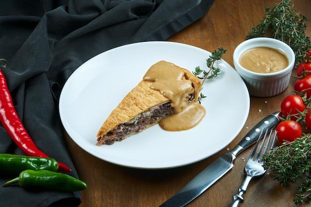 Klassiek amerikaans stuk van het rundvleespastei van de roker - het borststuk van de pindasaus op een witte plaat in een samenstelling met groenten. lekker gebak.