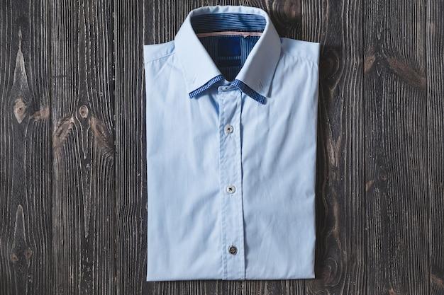 Klassiek blauw gevouwen katoenen herenoverhemd met lange of korte mouw op zwarte brute achtergrond
