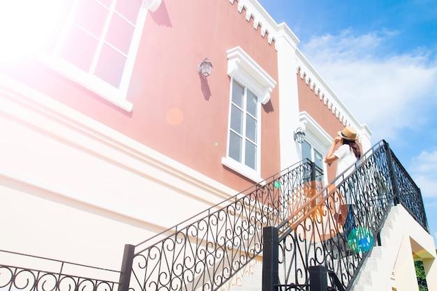 Klassiek gebouw met aantrekkelijk perspectief en toeristische vrouw in witte jurk en hoed