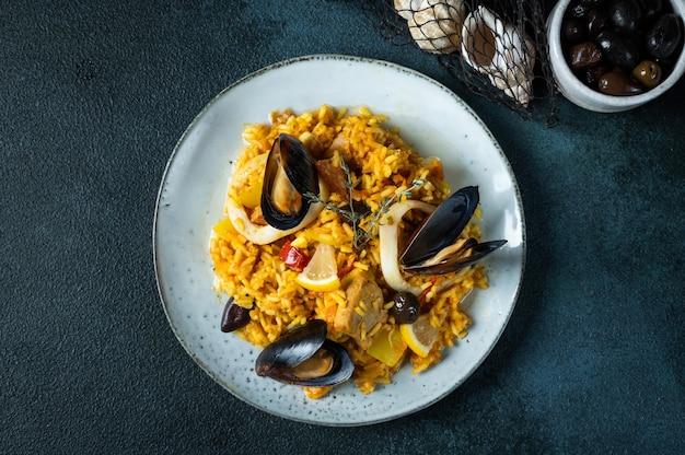 Klassiek gerecht van spanje, zeevruchten paella in plaat op blauwe achtergrond bovenaanzicht. spaanse paella met garnalen, klemmen, mosselen en verse citroen. spaans eten. troosteten. rijst met zeevruchten.