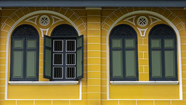 Klassiek groen houten venster bij het gele concrete gebouw.