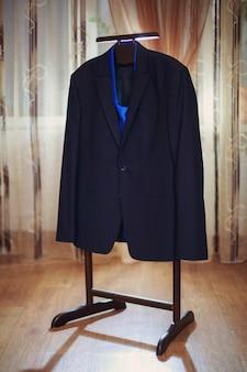 Klassiek herenjack met blauwe stropdas op de houten hanger in hotelkamer. designer heren jas met close-up binnen. etalage voor herenwinkel. herenkledingwinkel. mannelijke ochtend dicht omhoog