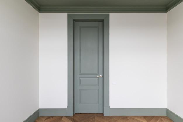 Klassiek interieur kleine kamer met franse visgraat parketvloer en groene deur en plinten de laatste fase van afwerkingswerkzaamheden in het appartement