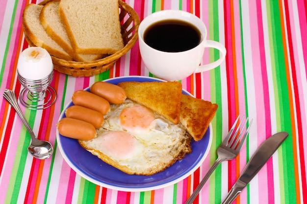 Klassiek ontbijt op gestreept kleurrijk tafelkleed