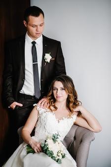 Klassiek portret van de bruid en bruidegom thuis tegen de achtergrond van de kamer. gelukkig dag jong koppel. het concept van de vakantie en liefde in het gezin. huwelijksvakantie.